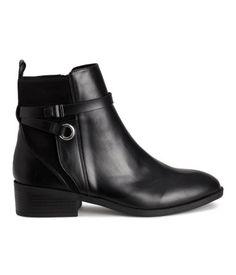 Sort. Et par boots i skinnimitasjon med detaljer i semsket skinnimitasjon. De har ankelhøyt skaft med hempe bak, dekorative remmer og glidelås i siden. Fôr