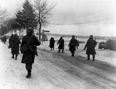 Troops of US 101st Airborne Division moving out of Bastogne, Belgium, 31 Dec 1944. (US Army Center of Military History)