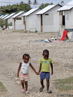 Two young children make their way through the Tabarre Issa Temporary Camp run by Irish non-governmental organisation Concern in Port-au-Prince, Haiti, on the second anniversary of the devastating earthquake that struck the Caribbean nation on 12 January 2010.