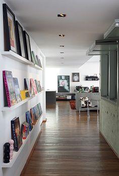 """Mesmo ampliado na reforma, o corredor ganhou prateleiras estreitas para expor livros, quadros e objetos. """"Meu marido não gosta de espaços claustrofóbicos, mas não queríamos deixar um paredão branco"""", conta a arquiteta Juliana Grave"""
