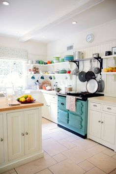 Aga & Kathryn Ireland decorated spacious white kitchen with turquoise oven/stove and bright colored dishes
