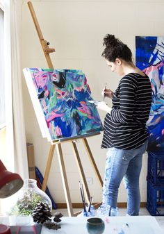 Canberra-based artist Skye Jefferys paints at her easel, in her home studio.
