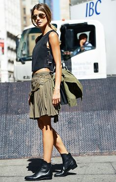 A crop top is worn with a pleated miniskirt, round sunglasses, and black ankle boots