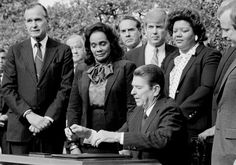 President Ronald Reagan signs the bill making Martin Luther King Jr.'s birthday into a national holiday, as Coretta Scott King watches, Nov. 2, 1983, ...