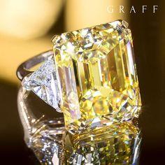 A hypnotic 38.13 carat emerald cut Fancy Intense yellow diamond ring casts mesmeric scintillation ...