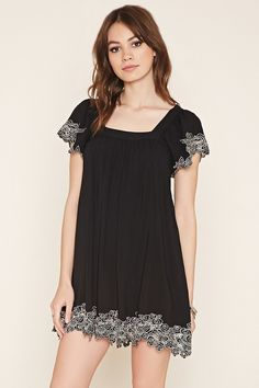 A woven dress with a square neckline, short sleeves, a cutout back accent, and contrast embroidery on the scalloped trim.