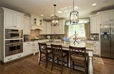 Traditional kitchen with painted white cabinets, a large kitchen island with room for 3 barstools, built in bench for the breakfast nook and desk with cork bulletin board. by Driggs Designs