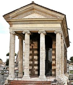 """Ancient Roman Temple of Portunus (Tempio di Portuno) in Piazza della Bocca della Verità, Rome (Italy) This temple has a previous and mistaken name: Temple of Fortuna Virilis (""""manly fortune""""). It was built in the 1st Century BC in the Ionic Order, which is fully represented in all details of this portico.  The temple was also a church for some of its history but is now an ancient monument. It has clearly been much restored, while still showing quite a bit of damage to its details."""