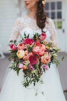 Lush, cascading bridal bouquet with coral peonies, peach ranunculus, and pink tulips // Nashville Wedding Florist #peachranunculus
