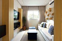 A sala de TV, de 7,67m², assinada por Cristina Bárbara, explora as paredes com armários suspensos, além da estante de formato escultural, que por si só decora o espaço.