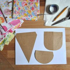 Tecidos com estampas diversas Tesoura Cola quente Molde da bandeirinha no formato de sua preferência Aviamentos para decorar as bandeirinhas Película termocolante para fixar tecido em tecido ou fita dupla-face