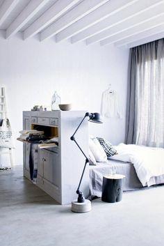 chambre blanche, lit avec tete de lit qui sert de séparateur d'espace, grandes poutres peintes en blanc, parquet gris, luminaire pliant en métal noir en style industriel, rideaux semi-transparents en gris clair
