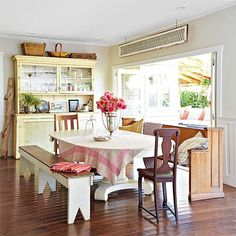 Hinged glass doors fold open to create one flowing space from the dining room to the porch, breaking the boundary between indoors and out. A unique assortment of furniture, all unified by rustic vintage charm, captures the lo