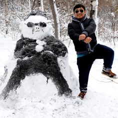 A man poses with a PSY Gangnam Style snowman  following a three-day snowstorm in Changchun, capital of northeast China's Jilin Province