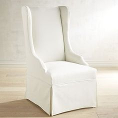 Crafted with a birch frame, foam padding and dressed in a removable, cotton slipcover, our Aislin Dining Chair has a high back, curvy arms and a tailored skirt giving it a pretty demeanor with a no-nonsense attitude.
