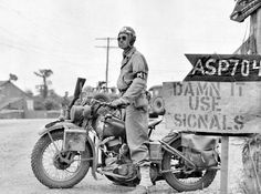 American Military Police on a Harley-Davidson WLA motorcycle at a crossroads near Saint-Lô, 1944.
