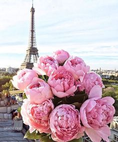 The Eiffel Tower in Paris, France with a bouquet of pink peonies in the foreground.