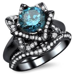 Blue Diamond Lotus Flower Engagement Ring Bridal Set - This is an incredible & unusual 2.0 carat Blue Diamond Lotus Flower Engagement Ring Bridal Set stamped in 14k Black Gold. It features a AAA quality 1.05 carat Blue Round Diamond set atop of the ring. It has .45 carats of white diamonds that surround the solitaire & .50 carats are set on the band. They are a grading of SI1–SI2 & a G in color. The top measures 13.5mm wide. All of diamonds are 100% natural & is enhanced…