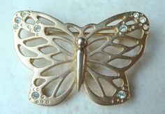 A pretty vintage golden butterfly brooch.  The butterflies wings are made from textured gold tone metal, in contrast the body of the butterfly is smooth. The wings have clear rhinestone detailing at each wing tip. Circa 1970's.