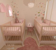 Habitación infantil para mellizas con el rosa omnipresente y con vinilos decorativos mariposas que reviste la pared de las cunas dándole entidad marcando la zona de los cabezales.