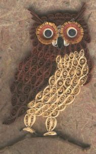 Quilled owl sitting on twig, background is handmade paper. His eyes are wrapped with 2 fringed layers.