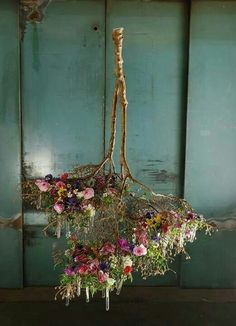 Inverted branches draped with mixed fresh flowers