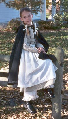In childrens pioneer clothing, the Daisy dress is shown and buttons down the front. The cape has a lined hood.  An apron and pantaloons are included.