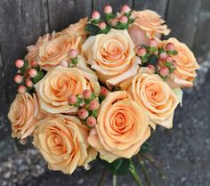 Coral rose and berry bouquet by Holly's Wedding Flowers.