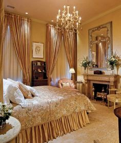 This is a luxurious bedroom with a handsome fireplace,large windows with custom draperies and beautiful chandelier.The bed linens and upholstered pieces are gorgeous.