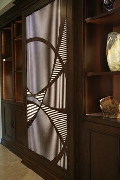 A unique laser cut wood panel is both art and a cover for hidden storage, in this cabinet by Vicki Blakeman Interior Design.