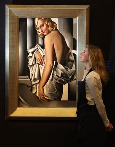 A gallery technician at Sotheby's auction house admires a painting by Tamara de Lempicka entitled 'Portrait de Marjorie Ferry' from 1932, wh...