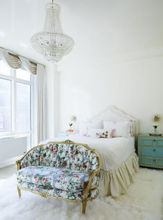 This whimsical white 18th-century French-inspired master bedroom is peaceful and Parisian with a floral print sette and crystal chandelier.