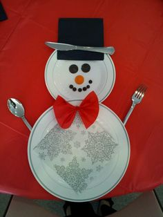 Christmas snowman place setting. Dinner plate, dessert plate, black dinner napkin for hat, red dessert napkin for tie. Candy pieces for face.