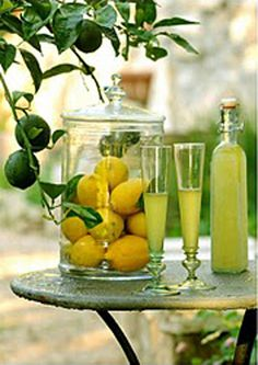 love this presentation for a tiny limoncello bar, for a countryside wedding - with lemons in large jar and non commercial limoncello in old fashioned bottle