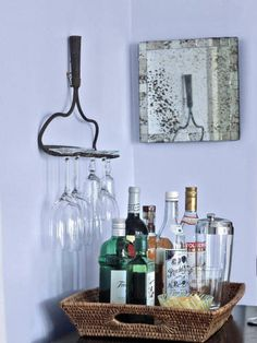 Convert a cramped corner into a fully stocked bar by hanging a rake over a small table and suspending stemware from its tines.