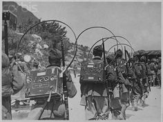 A radio-telegraph unit of the Italian army marches on maneuvres with portable radios.