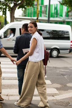 Womenswear Street Style by Ángel Robles. Fashion Photography from Milan Fashion Week. Woman wearing a comfy summer outfit: white shirt, wide leg pants and leather mini backpack.