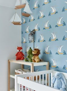 Blue boy's nursery features a white crib placed beside a two toned changing table lit by a caged sconce located under a sailboat mobile hung in front of a wall covered in Katie Ridder Beetlecat Wallpaper.