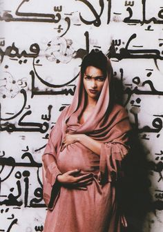 In May of 1995 Paris-based Tunisian designer Azzedine Alaïa created a Middle Eastern inspired hooded cloak as a maternity dress for Farida Khelfa, his close friend and muse. She was photographed in front of a large mural painted in Arabic calligraphy at the Musée national des Arts d'Afrique et d'Océanie in Paris