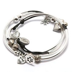 The Mini Lucky leather wrap bracelet features 2 strands of leather with silverplate crescents and a large secure silverplate lobster clasp. Handmade in the USA and designed to be worn as a charm bracelet only. The Mini Lucky includes 4 charms- lucky, silver heart, paw print and i love my dog charms.