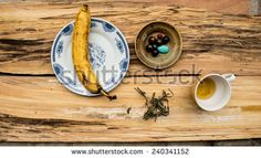 Banana and cup of tea on wooden table - stock photo