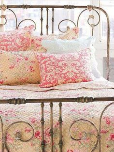 Ornate iron bed frame with country pink linens is beautiful and so inviting!