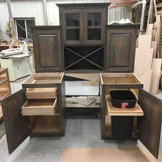 Custom dry bar with pull out trash can draws on the other side three top cabinets one with glass doors and a wine rack below stain and finished in dark grey#entertainmentcenter#lnk #vanity #customwoodworking #kitchencabinets #classicwood via ClassicWoodLincoln.com