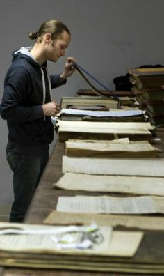 In this Feb. 26, 2014 photo, Monroe County archivist Jon Weiler works on repairing and protecting aging county records in Bloomington, Ind. ...