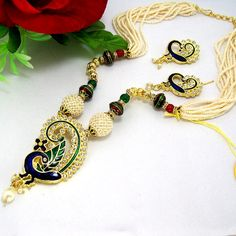 This antique pipe necklace is based on designer jaal puwai chid balls which provides an ethnic look to the neck wear. The necklace is based on jaal puwai balls which are decorated with tri colored seeds and separated with lustre round balls and octan stone separators. The earring are also based on jaal puwai ball, octan stone separator and lustre round balls.