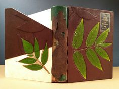 Simplified binding by Cara Schlesinger. Pergamena goat over boards laminated w/ 1-ply bristol, relief of ailanthus leaf & inlaid w/ ailanthus leaves; Harmatan morocco on spine w/ onlaid London planetree bark lined w/ Stonehenge & sekishu; herringbone-sewn text block w/ double folio sewn-on endsheets strengthened w/ sekishu; spine lined w/ sekishu, 2 layers of airplane cotton, & Harmatan morocco to match outer spine; linen endbands over rolled leather core; pastepaper pastedowns of gingko…