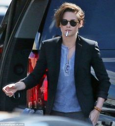 Light me up: Kristen Stewart pauses with a cigarette hanging from her lower lip while waiting for a light after arriving at a studio in Los Angeles on Wednesday