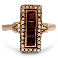 Victorian-era ring features an elongated rectangular design with a linear row of channel set garnets surrounded by a halo of elegant seed pearls