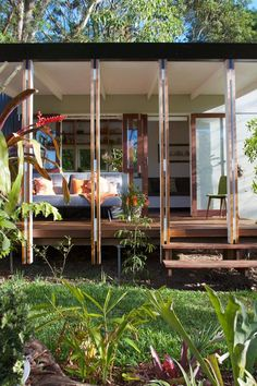This tiny house puts the sub-tropical climate to use with large windows and doors that open onto a deck.  All of the decking boards are recycled and the wood doors came from old Queensland cottages.