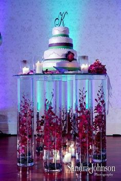 This is amazing! Cake display made with hige glass vases filled with orchids!